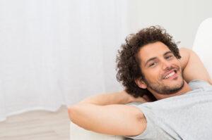 Happy Man Resting On Sofa